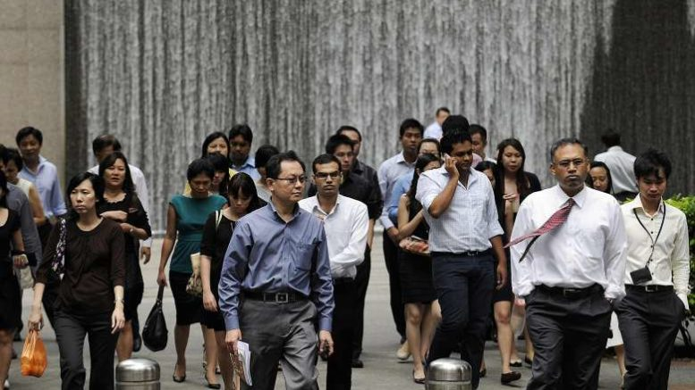 Office workers walk through the central business district during lunch break.PHOTO: BLOOMBERG