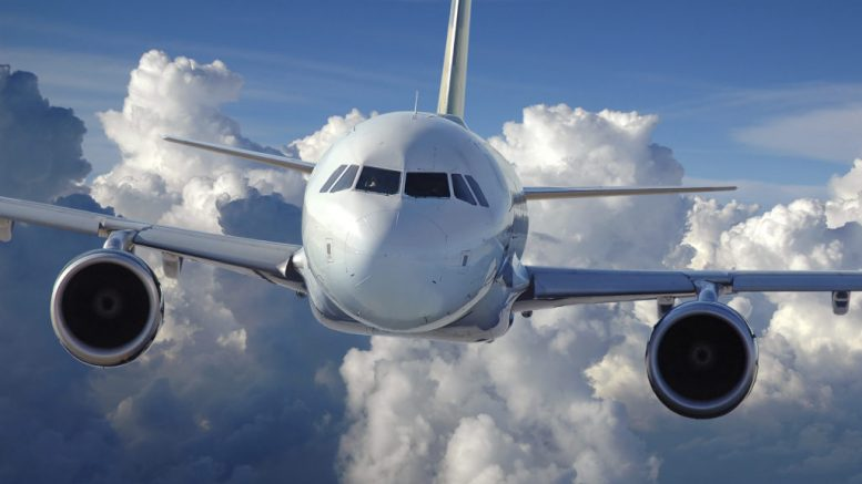 Commercial airliner in flight over a cloud covered background.